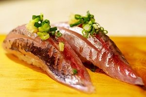 twee stukjes sushi met vis op houten plank