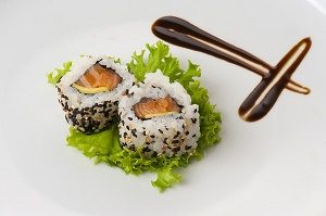 twee stukjes sushi met zalm op blaadje sla