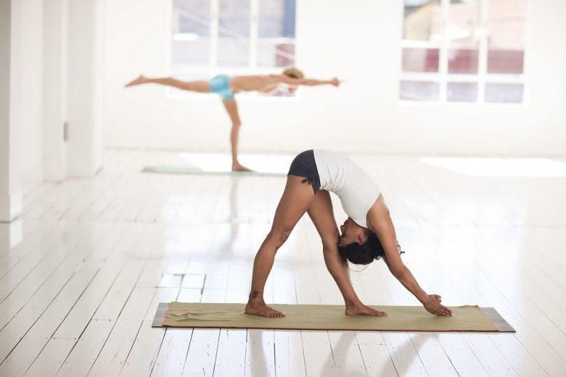 ruimte met veel daglicht en twee mensen die yoga doen