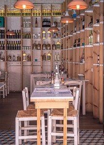 bar met tafels en stoelen en wijn in rekken langs muren