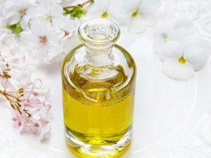 glazen flesje met massageolie en bloemen eromheen
