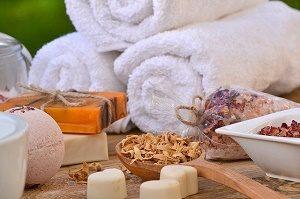 opgerolde handdoeken, zeepjes en badkruiden
