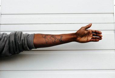 arm met tatoeage voor witte muur