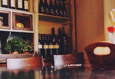 tafel met stoelen en flessen wijn in kast