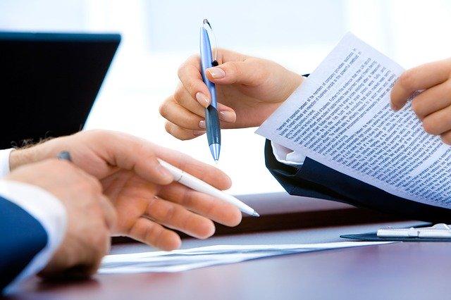 contracten op tafel met handen met pennen