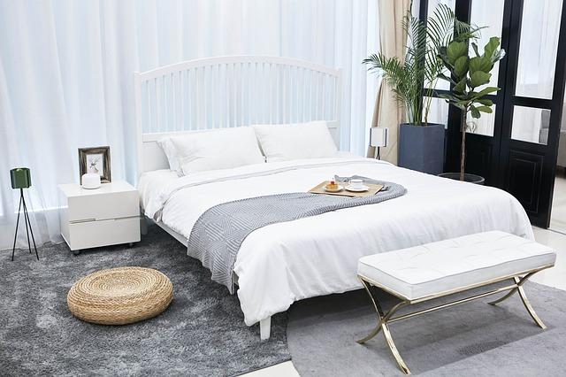 slaapkamer met wit gordijn en grijs vloerkleed