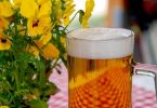 glass of beer and yellow violets