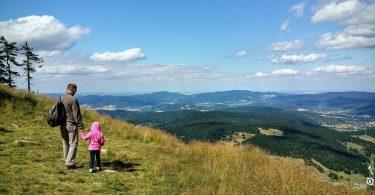 vader wandelt met kind door bergen