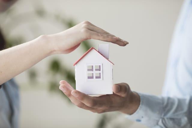 twee handen beschermen huisje