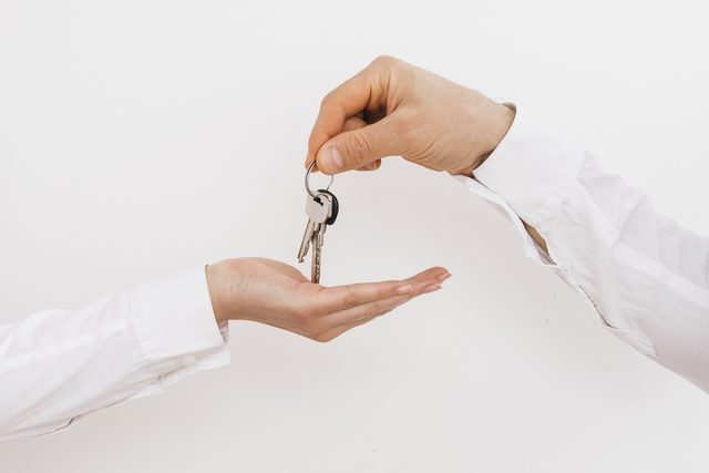 ene hand geeft andere hand set sleutels