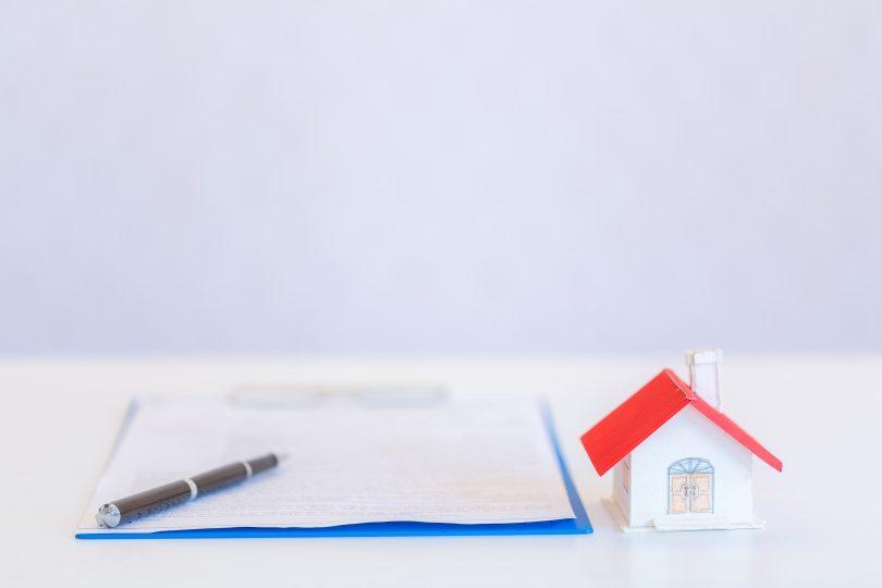 contract met pen en klein huisje met rood dak