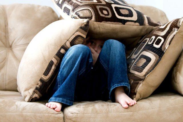 kind verstopt onder kussens