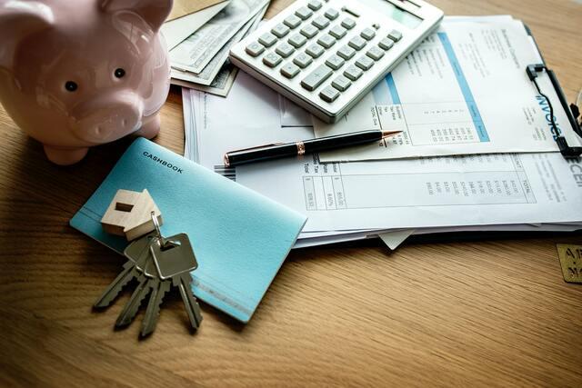 bureau met spaarvarken, calculator en papieren