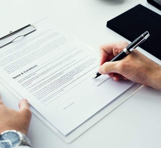 hand met pen ondertekend papieren