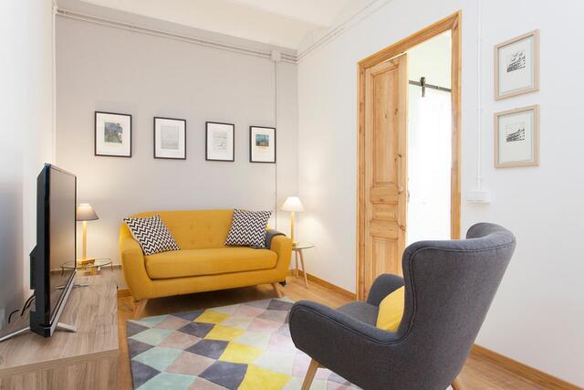woonkamer met gele bank en grijze fauteuil