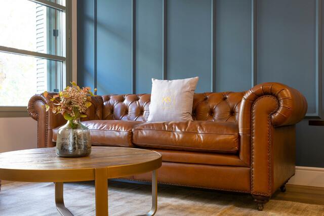 woonkamer met bruine leren bank en blauwe muur