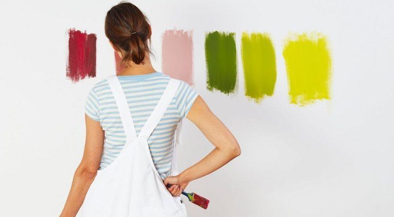 vrouw staat voor 6 testkleuren op de muur