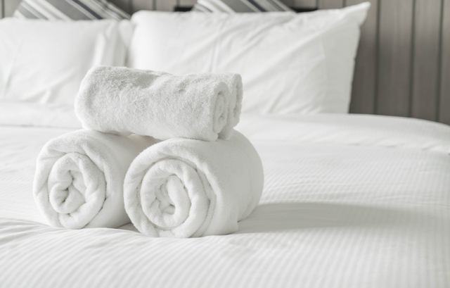 handdoeken opgerold op bed