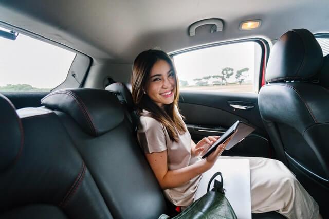 dame zit in auto met tablet