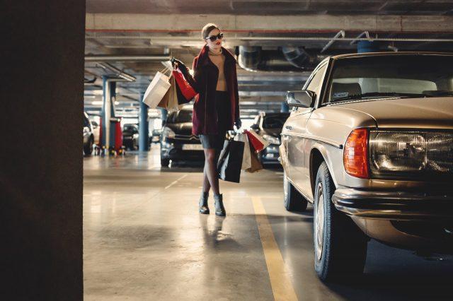 dame loopt in parkeergarage naar auto
